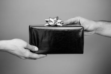 black and white image of one hand giving a gift to another hand
