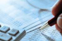 close-up of business forms, calculator and pen tip