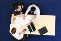 three people meeting around a table, from above